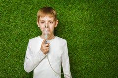 Boy in white breathing through inhalator mask Royalty Free Stock Photos