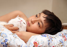 Boy with white cat. Asian boy with white cat lieng in bed Stock Images