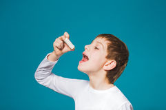 Boy in white clothes eating a lot of pills Royalty Free Stock Photo