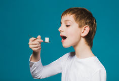 Boy in white clothes eating pills from spoon Royalty Free Stock Photos