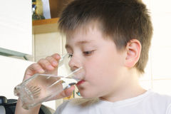 Boy in white drinks water Royalty Free Stock Images