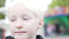 Boy with white hair close-up. Boy dreamily looks ahead, rolls his eyes and dreams of something. On the street it is cool, on the child a jacket. In the stock video footage