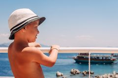 A boy in a white hat holding the railing on the ship and looking at the sea stock image