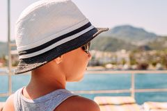 A boy in a white hat looking at the sea. summer stock photography