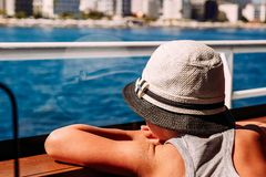 A boy in a white hat looking at the sea through the window of the ship royalty free stock photography