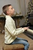 Boy in white knitted jumper at the piano Stock Photos