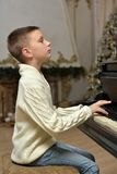 Boy in white knitted jumper at the piano Royalty Free Stock Photos