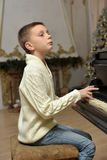 Boy in white knitted jumper at the piano Stock Photo