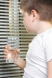 Boy in white looking to window Royalty Free Stock Image