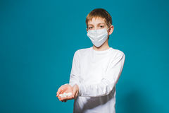 Boy in white protection mask holding pills Royalty Free Stock Photos