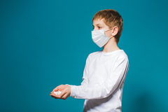 Boy in white protection mask holding pills in hand Royalty Free Stock Photo