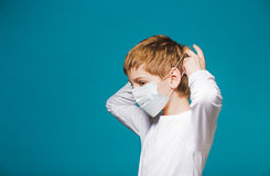 Boy in white putting on protection mask Stock Photography