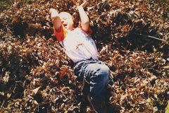 Boy in White and Red Shirt Lying on Brown Leaf during Day Time Stock Photography