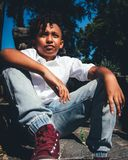 Boy in White Shirt and Faded Blue Jeans Sitting on Ground stock photos