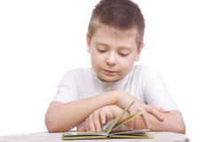 Boy in white shirt reading book Royalty Free Stock Photography