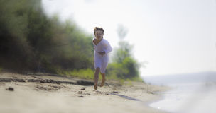 Boy in white shirt, running along the river bank Stock Images