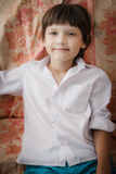 Boy in white shirt sits at home royalty free stock photo