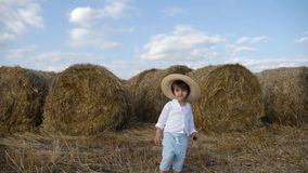 Boy in a white shirt and a straw hat is barefoot on a sloping field. At the stacks at sunset stock footage