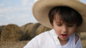 Boy in a white shirt and a straw hat is barefoot on a sloping field. At the stacks at sunset stock video