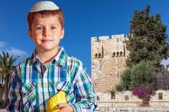 The boy in white skullcap with etrog. Sukkot in Jerusalem. Charming seven year old boy in white festive skullcap with etrog Royalty Free Stock Photo