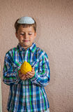 The boy in white skullcap is holding etrog. Etrog -  ritual fruit for the Jewish holiday of Sukkot. Beautiful seven year old boy in white knitted skullcap is Royalty Free Stock Photo