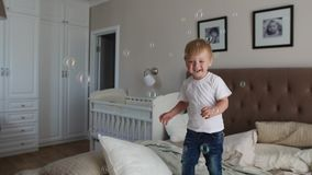 A boy in a white T-shirt and blue jeans catches soap bubbles standing on the bed in the parent bedroom.  stock video