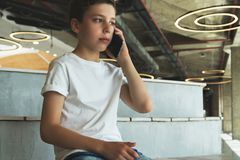 Boy in white t-shirt is sitting indoors and talking on his mobile phone. A teenager uses a cell phone, calling, phoning Stock Photo