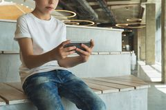 Boy in white T-shirt and sunglasses sitting indoor and uses smartphone. Teenager plays computer games on digital gadget. Front view.Boy in white T-shirt and Royalty Free Stock Photo