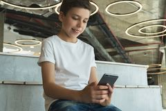 Boy in white T-shirt and sunglasses sitting indoor and uses smartphone. Teenager plays computer games on digital gadget. Smiling boy in white T-shirt and Royalty Free Stock Image