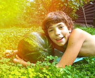 Boy with whole water melon lay on the green grass Royalty Free Stock Image