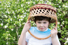 Boy with  wicker basket on his head in the spring garden Royalty Free Stock Photography