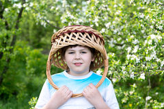 Boy with  wicker basket on his head in the spring garden Stock Images