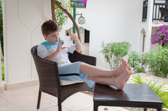Boy in  wicker chair on the terrace Royalty Free Stock Image