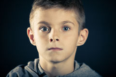 Boy With Wide Open Eyes Staring at the Camera. Close up Face of an Angry Boy With Wide Open Eyes Staring at the Camera Against Dark Blue Background Stock Photo