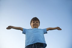 Boy with widely placed hands on background of  sky Royalty Free Stock Images