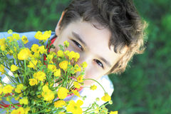Boy with wildflowers. Child with wildflowers in the garden Stock Photos
