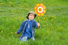 Boy in the wind. Young boy playing in the grass on a windy spring day stock photo