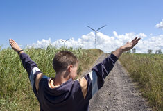 Boy and wind turbine. A teenage boy standing on a country dirt road with a huge wind turbine in the distance holding his arms high, imitating the shape of the stock photography