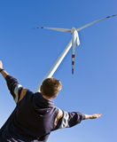 Boy and wind turbine. A teenage boy standing at a huge wind turbine holding his arms high, imitating the shape of the windmill's blades royalty free stock photo