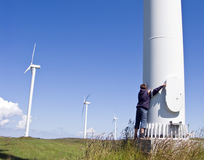 Boy and wind turbine. A teenage boy standing at the foot of a giant wind turbine, embracing it and looking up, more windmills in the background Stock Photography