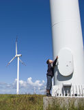 Boy and wind turbine. A teenage boy standing at the foot of a giant wind turbine, embracing it and looking up, another windmill in the background Royalty Free Stock Photography