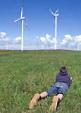 Boy and wind turbines. A teenage boy lying down on green grass of a meadow, looking at wind turbines in the distance. Green environment concept Stock Photos