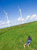 Boy and wind turbines. A teenage boy lying down on green grass of a meadow, looking at wind turbines in the distance. Green environment concept Royalty Free Stock Photography