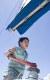 Boy (8-10) winding rope pulley of boat rigging on deck of sailing boat out at sea, smiling, low angle view Royalty Free Stock Photography