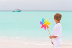 Boy with windmill on beach Stock Photo