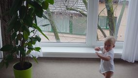 The boy at the window. The baby boy is looking in the big window stock footage