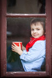 Boy on the window, laughing and drinking tea Stock Images