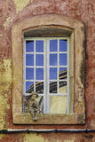 A boy at a window. Photo showing a window on a red painted wall Royalty Free Stock Photo