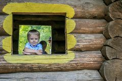 A boy in the window of wooden building at playground.
