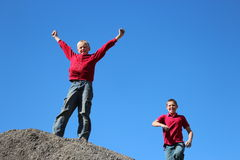 Boy winning. Boy on top of hill with another boy chasing Royalty Free Stock Photos